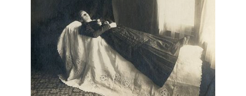 A post-mortem photo of a corpse on display, possibly for a wake, late Victorian.